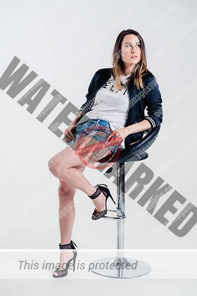 female model leaning on a chair